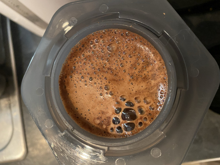 A birds-eye view of an Aeropress chamber sitting on a kitchen counter in which coffee is brewing
