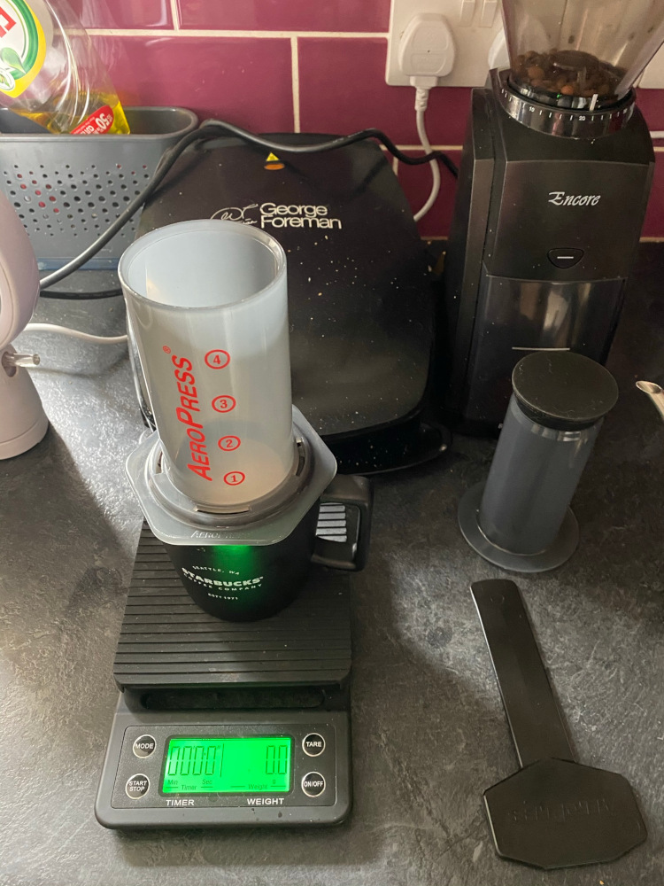 An Aeropress brewing chamber on top of a black mug in a kitchen