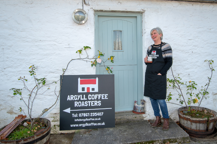 Eve from Argyll Coffee Roasters standing in front of a building next to a sign