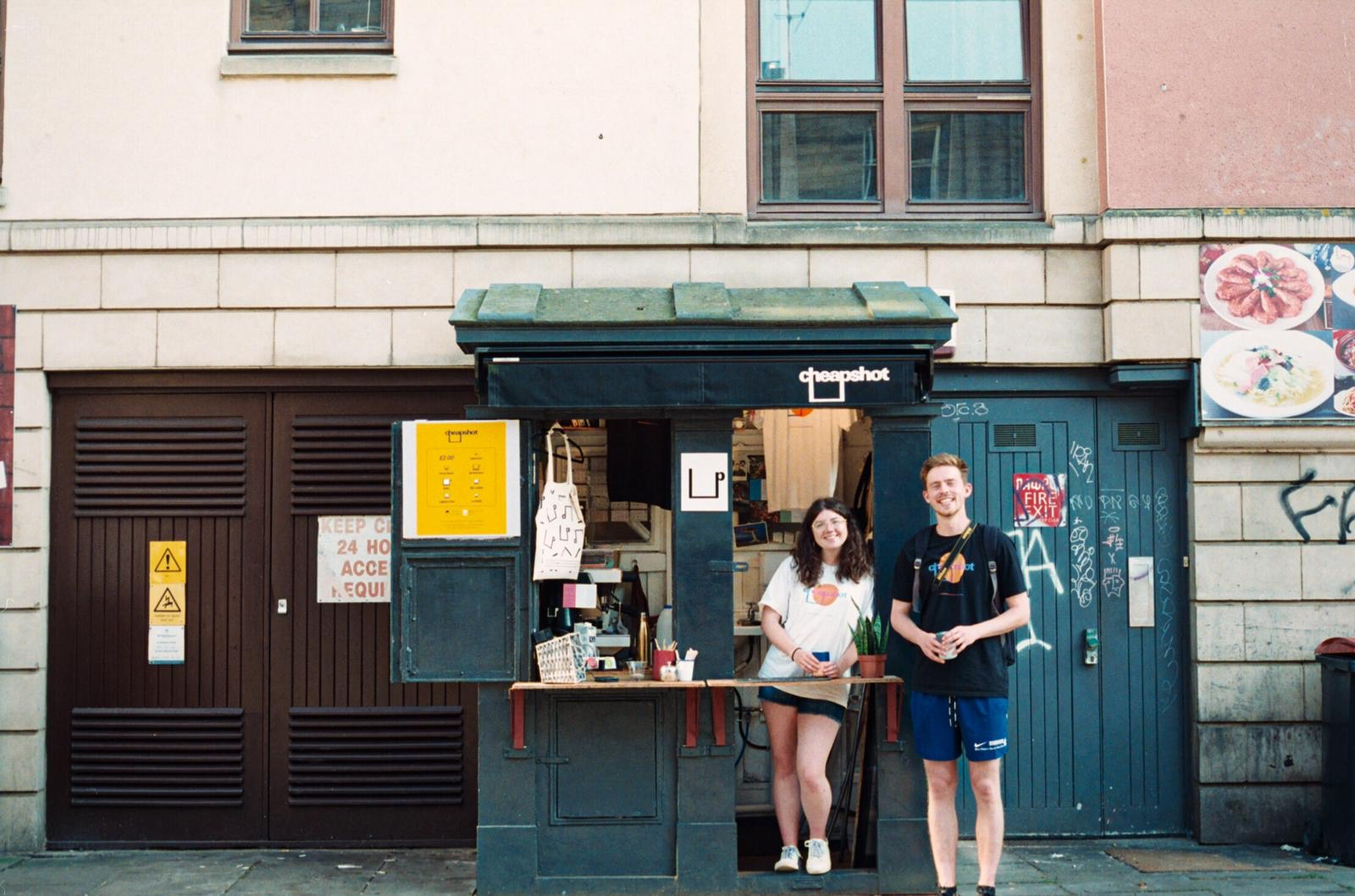 Two people standing in front of the Cheapshot police box cafe on a street