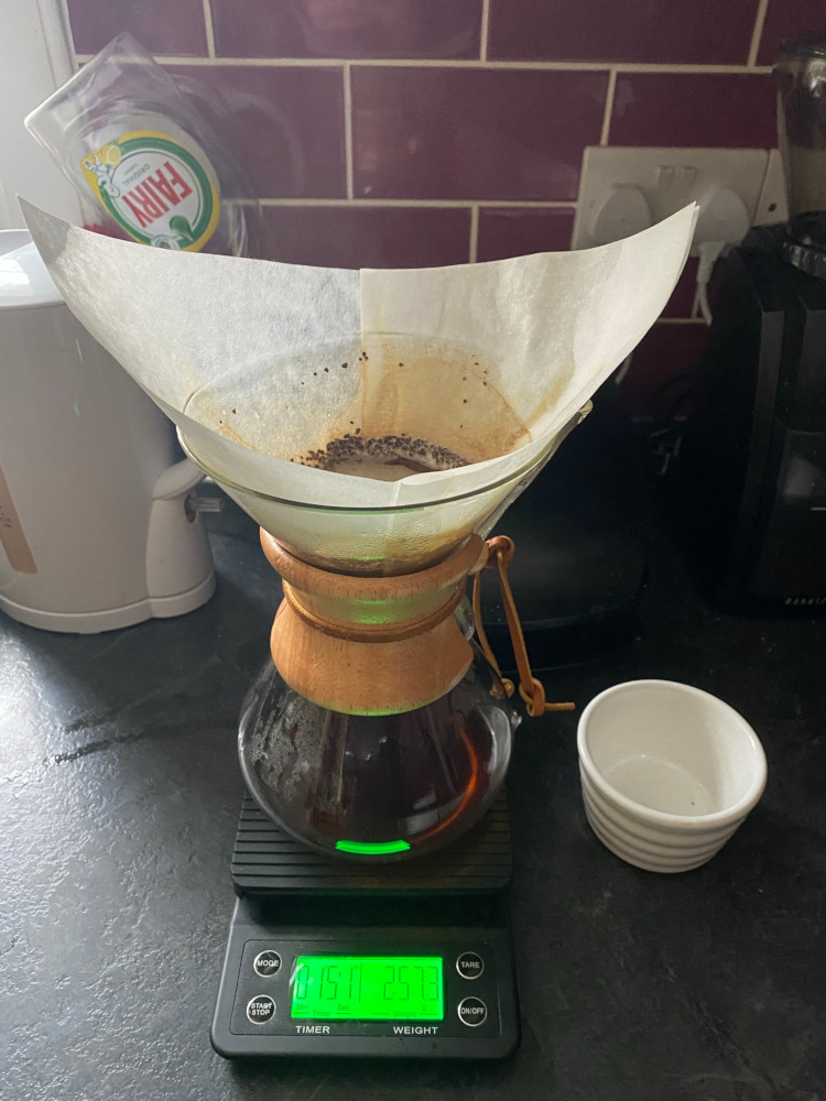 A Chemex containing coffee sitting on a scale in a kitchen