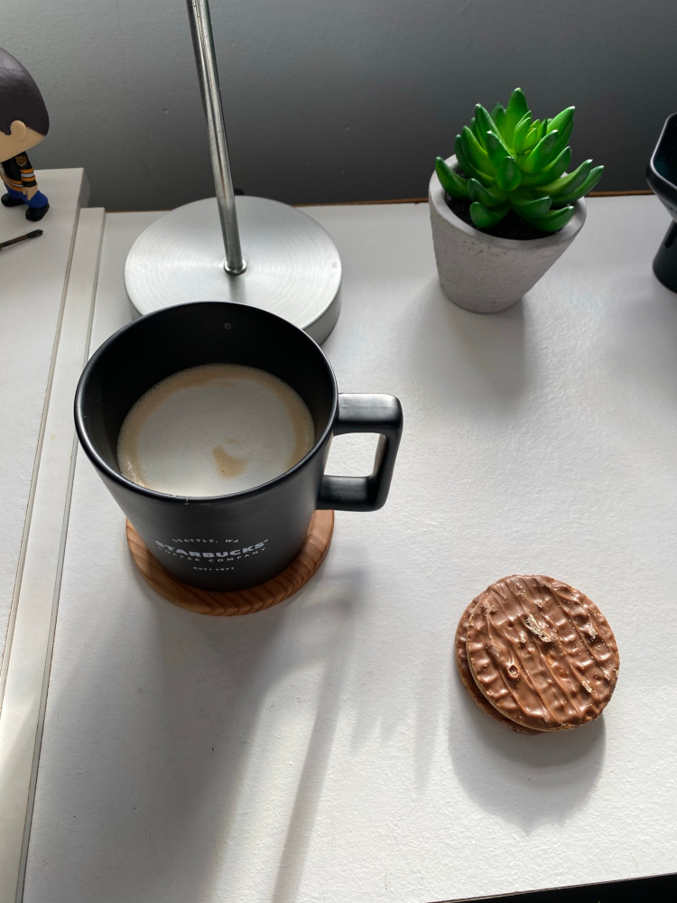 A cappuccino in a black mug next to two digestive biscuits on a white table
