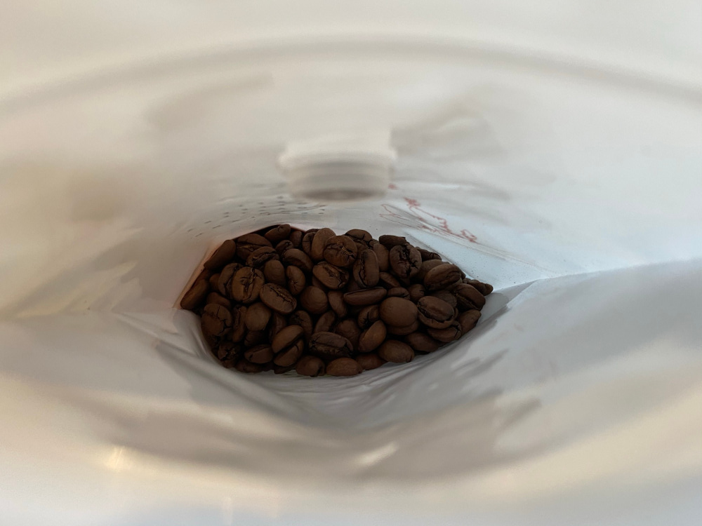 Coffee beans inside a bag with an Aeropress scoop resting on the beans