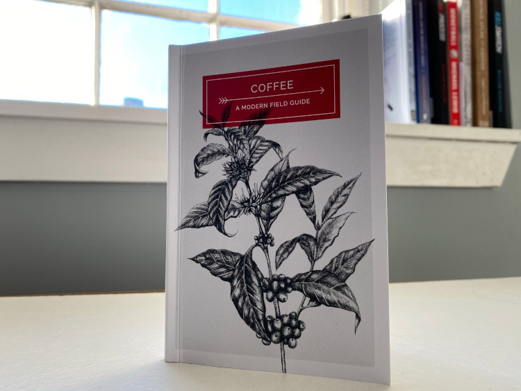 Coffee: A Modern Field Guide standing on a white table in front of a window and a selection of books