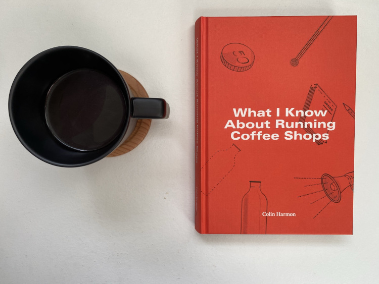What I Know About Running Coffee Shops book on a white table next to a cup of coffee