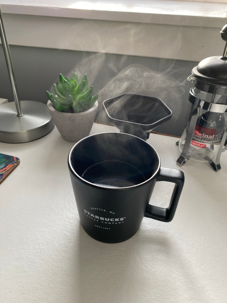 A coffee cup with steam coming out the top, sitting on a white table