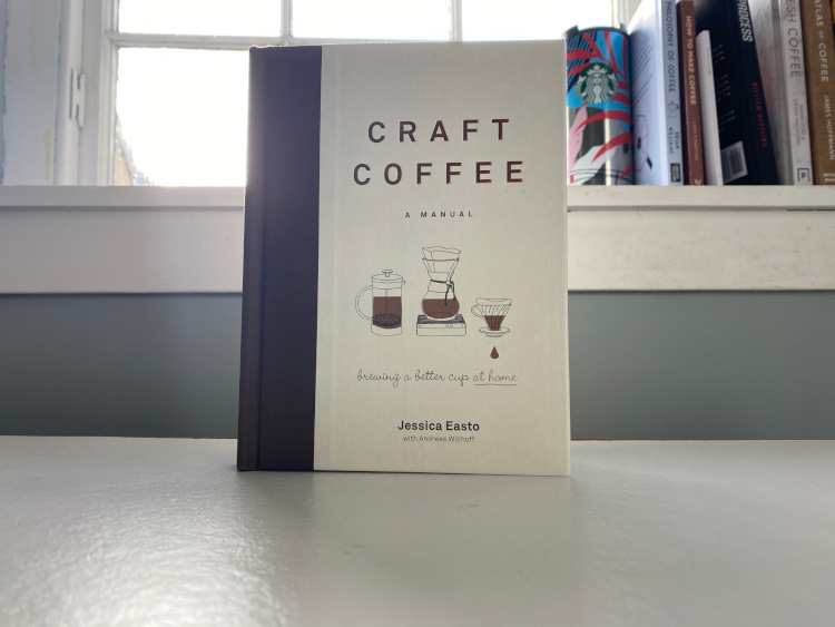 Craft Coffee: A Manual book sitting on a white table in front of a window and a collection of books