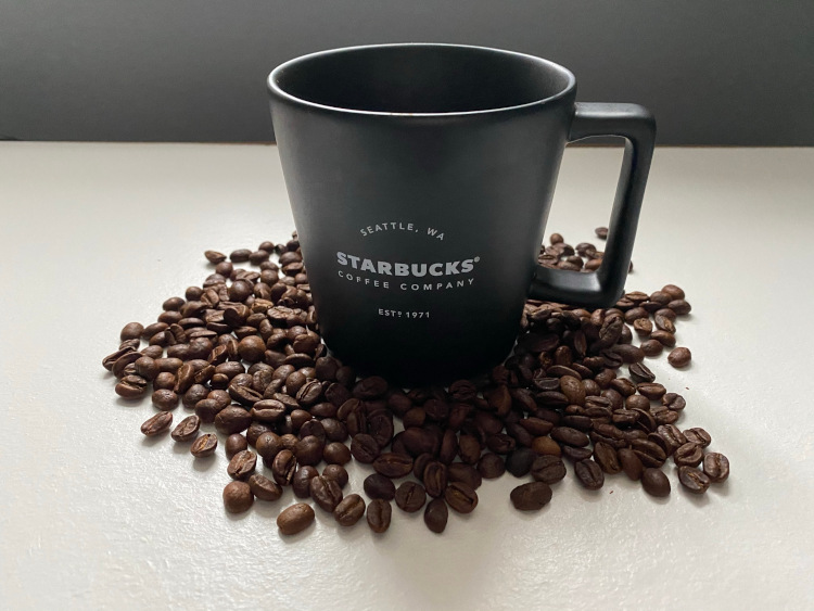 A black Starbucks cup surrounded by roasted coffee beans on a white table