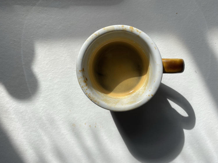 An espresso in a cup on a white table