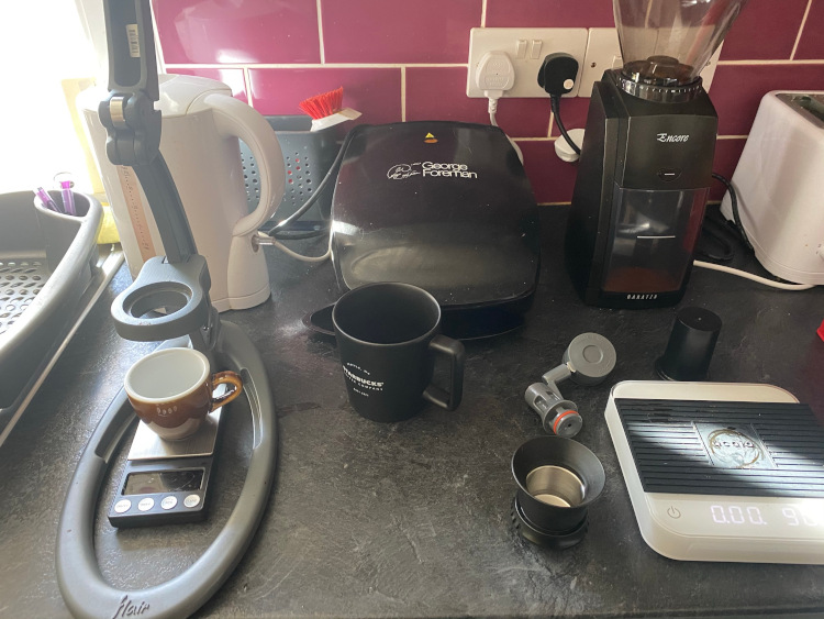 A Flair NEO on a kitchen counter next to a grinder, mugs, a set of scales, and other coffee equipment