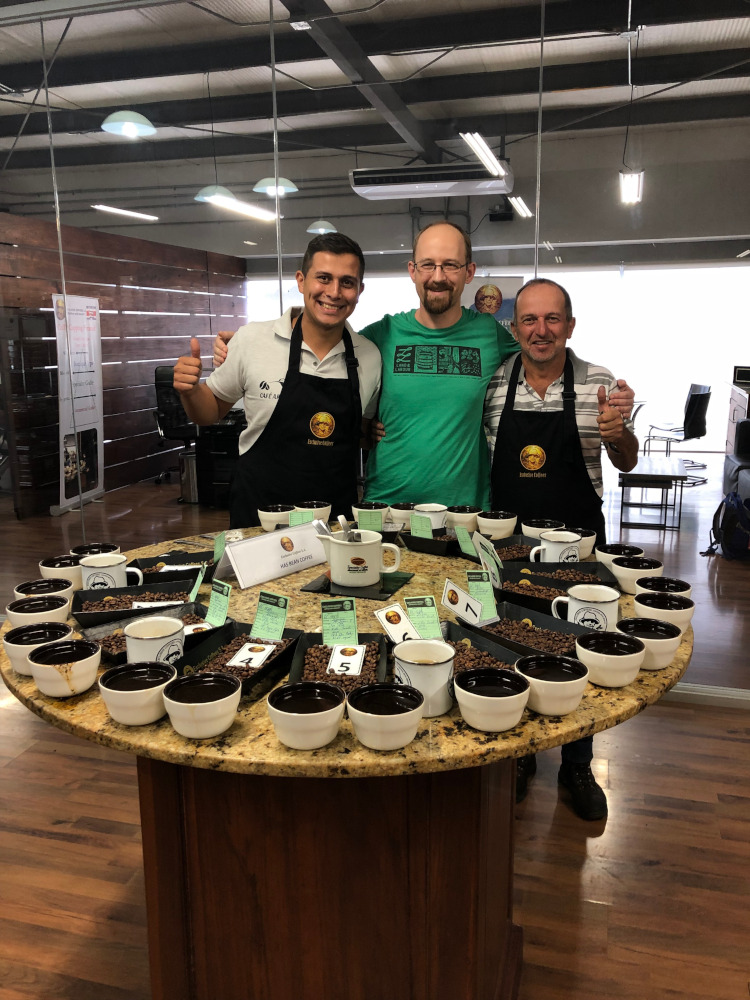 Roland from Hasbean standing between two people in a cupping room