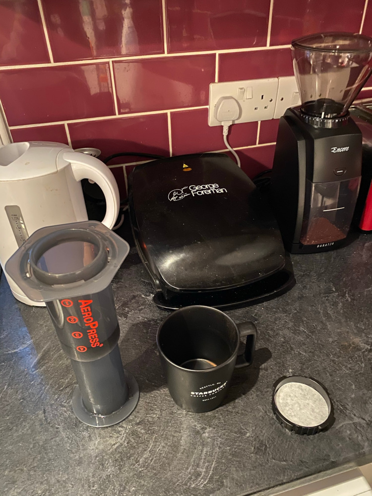 An Aeropress, mug, kettle, and coffee grinder sitting on a kitchen countertop