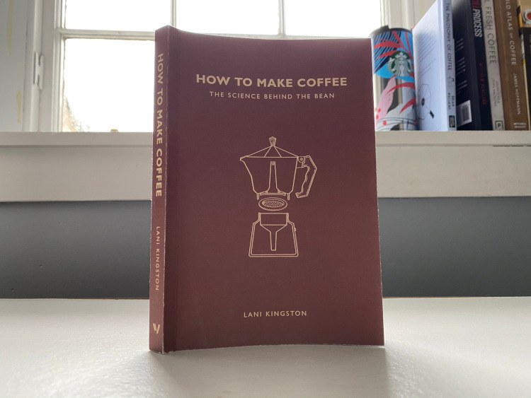 How to Make Coffee book standing on a white table in front of a window and books