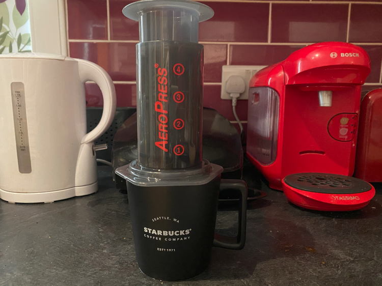 An Aeropress sitting on top of a Starbucks cup in front of kitchen equipment