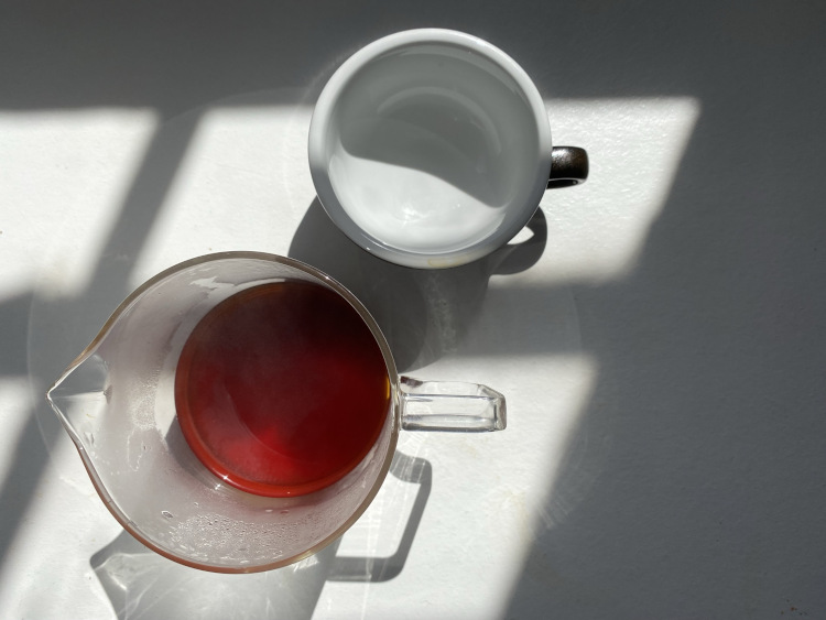 A glass jug that contains coffee next to a cup on a white table