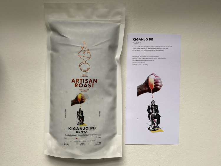 A bag of Artisan Roast Kenya Kiganjo beans, sitting on a white table in front of a window and books
