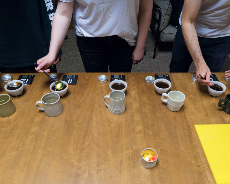 Five cupping bowls sitting on a wooden table in front of three people