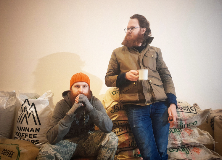 Alex and Lukasz, the founders of Manifesto Coffee, sitting next to bags of coffee
