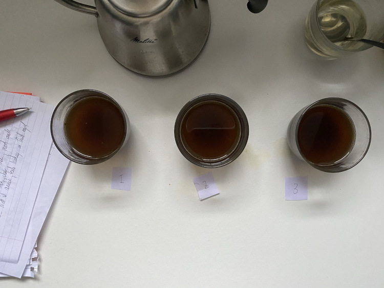 Three glasses containing coffee sitting on a white table
