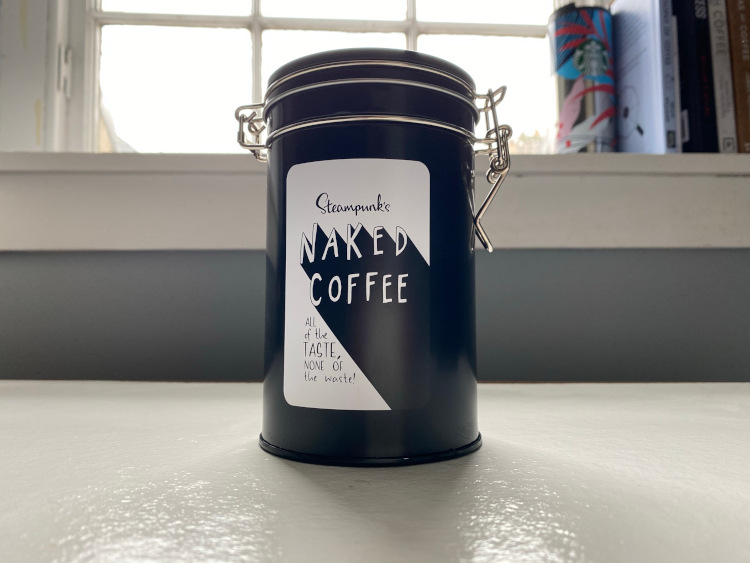 A black coffee tin sitting on a white table in front of a window
