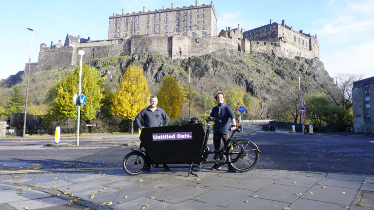 Callum and Alex, the founders of Untitled Oats, standing behind an Untitled Oats cart in Edinburgh
