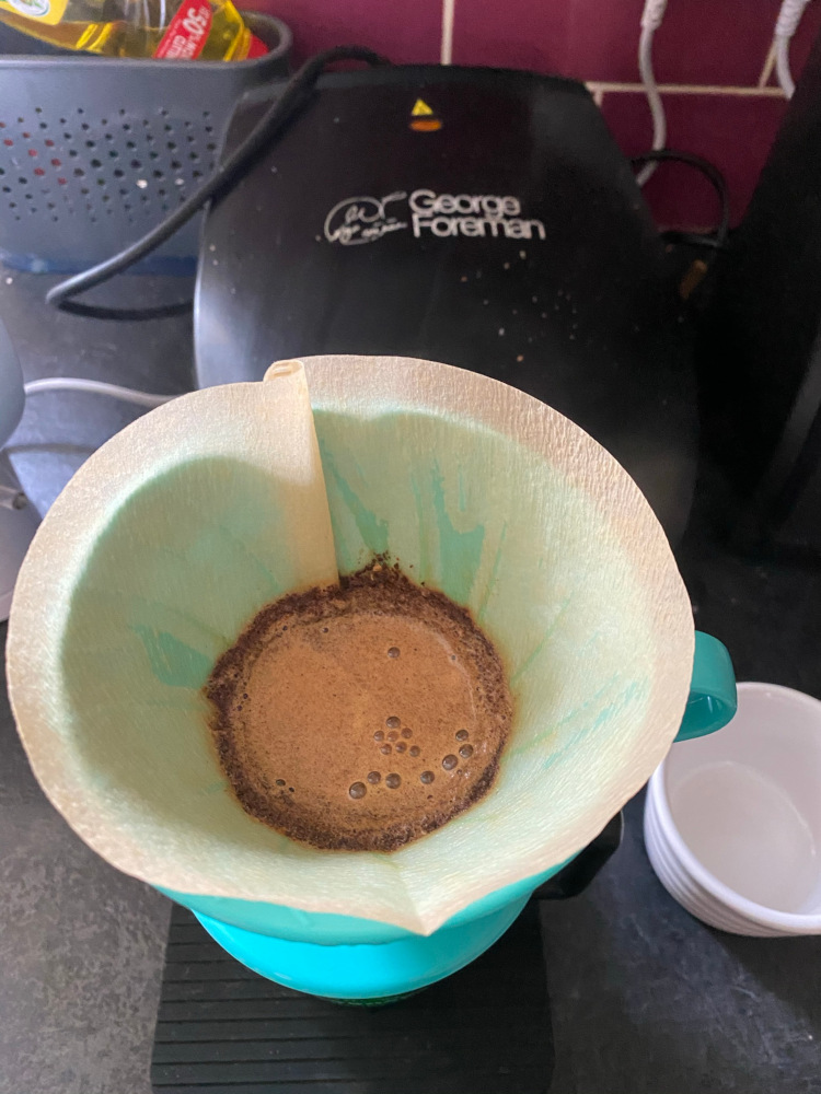 A turqoise Hario V60 on a black cup in a kitchen